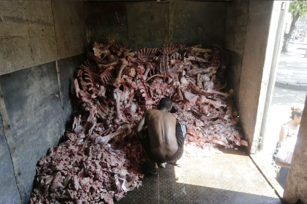 Un brasilero revolviendo carne podrida para poder comer (O Globo / Domingos Peixoto)