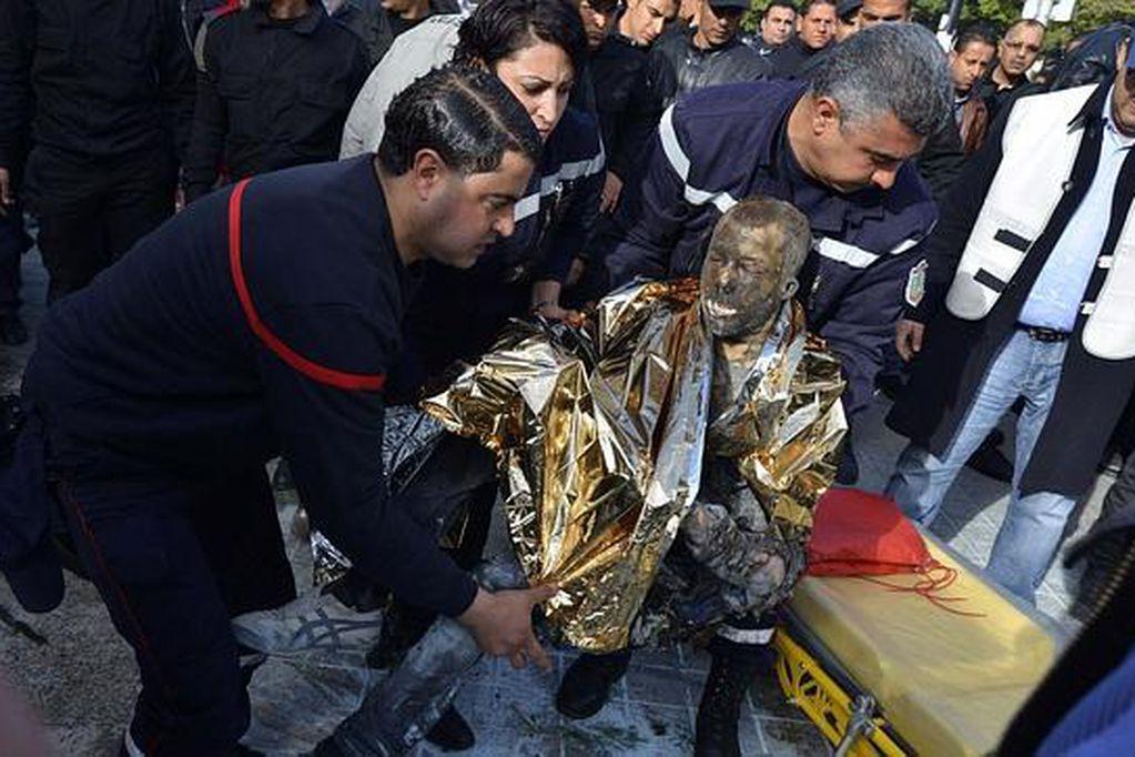 Varios peatones intentan ayudar a un hombre, después de que este se prendiera fuego, en el centro de Túnez. Gentileza / rfi